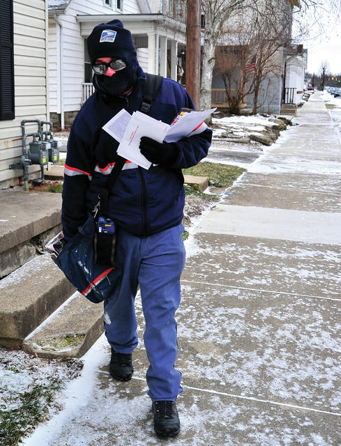 Piqua mail carrier Josh Stager is bundles up for the weather conditions as he delivers his route on Park Ave. in Piqua on Tuesday morning. Falling temperatures and high winds have prompted wind chill warnings across the midwest.
