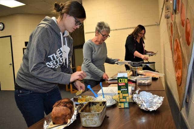 Cody Willoughby | Troy Daily News From left, Victoria Elliott, of Laura, and Eva Coughnour and Dana Chamberlin, of West Milton, indulge in a smorgasbord of carry-in goodies during the inaugural session of the Cookbook Club on Tuesday at Milton-Union Public Library.