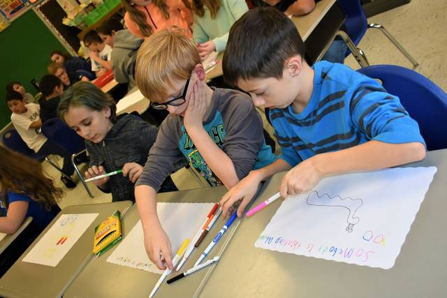 "Cody Willoughby | Troy Daily News From left, Cayson Gessner, Jordan Nutt, and Tristian Campbell draw original placemats to donate to organizations within the community during ""Kindness Week"" on Monday at Kyle Elementary in Troy."