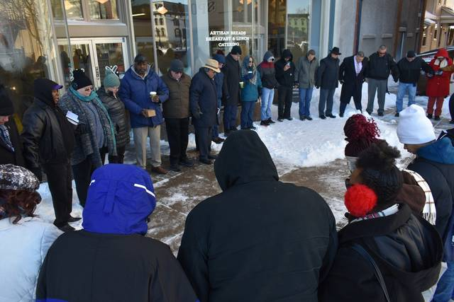 Cody Willoughby | Troy Daily News Participants hold hands during prayer in the southwest quadrant of the Public Square ahead of the annual Dr. Martin Luther King, Jr. Day march on Monday in Troy.