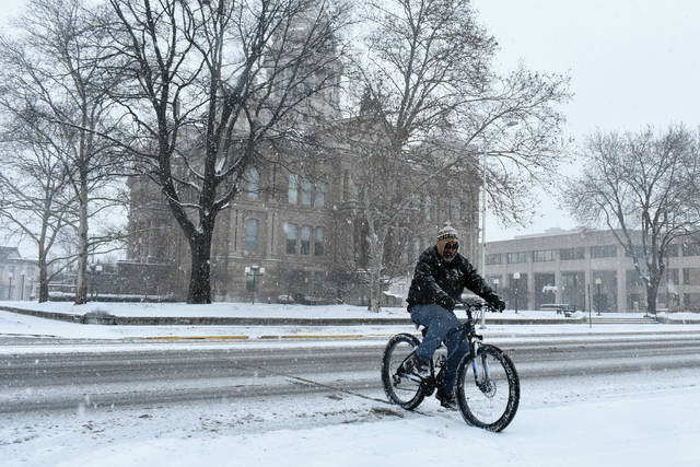 Cody Willoughby | Troy Daily News Terry Lucas, of Troy, rides his bicycle through heavy snowfall on Saturday in downtown Troy. The first major snowfall of 2019 is projected to bring 4-6 inches of accumulation to the Miami Valley through Sunday morning.