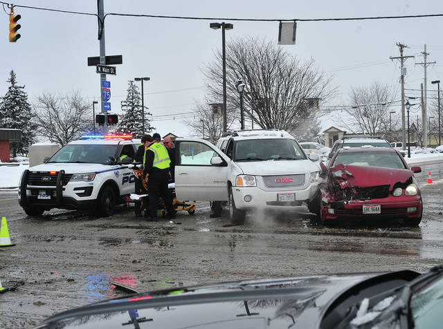 Medics prepare to move a crash victim to a waiting medic on Friday following a crash at the intersection of County Road 25-A and State Route 571.