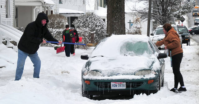 The theme of the day on Friday was clearing snow. A pair of Park Avenue residents brush snow from a vehicle while two boys carrying shovels make their way down the sidewalk searching for snow shoveling work.