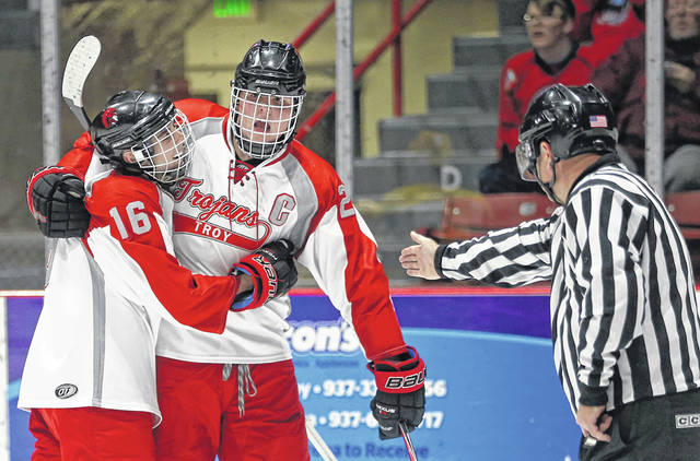 Lee Woolery|Miami Valley Sunday News Troy senior Jack McGuirk (20) is congratulated by teammate Zak Uhlenbrock (16) after scoring a goal during the Trojans' Senior Night game against Sycamore Saturday at Hobart Arena.
