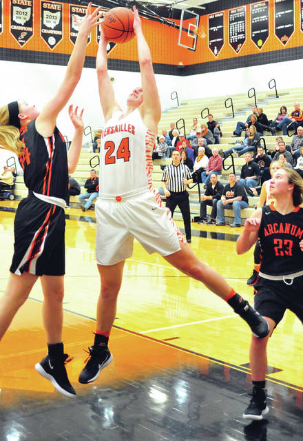 Versailles' Liz Ording pulls down a rebound against Arcanum's Taylor Gray as Gracie Garno looks on Tuesday night.
