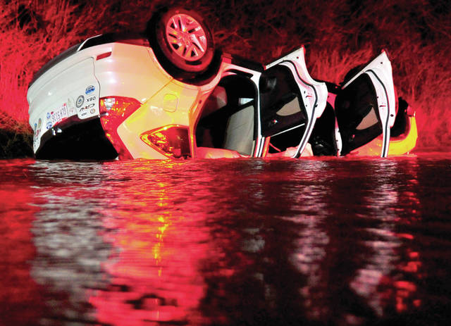 A car lies, overturned in high water, on St. Rt. 202 near Ebberts Road on Thursday following a crash which left the driver trapped.