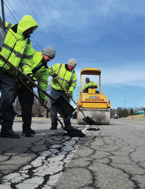 Mike Ullery | Miami Valley Today Piqua street crews make their way down Looney Road on Friday as they use cold patch to attempt to keep up with the ever-growing number of potholes on area highways.