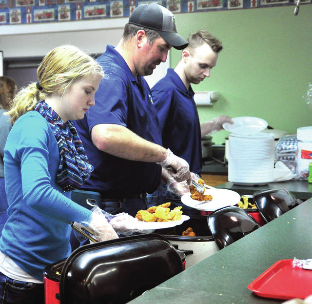 Mike Ullery | Miami Valley Today Fletcher Volunteer Fire Department volunteers, Jackie Bensman, Shane Miles. and Caleb Everett, l-r, serve fried fish to a steady line of hungry guests at the Fletcher Fire Department Fish Fry at their fire station on Saturday.