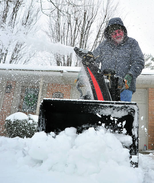 Steve Wills of Piqua clears his driveway with a snowblower on Wednesday morning following an overnight snow storm that dropped several inchces across the area.