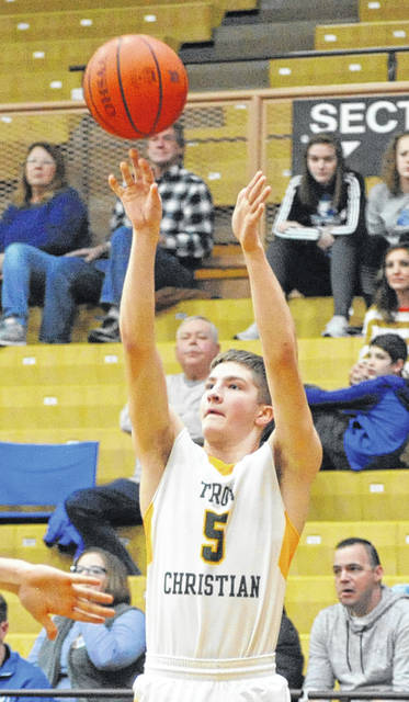 Josh Brown|Miami Valley Sunday News Troy Christian's Isaac Gray hits one of his five 3-pointers during Saturday's Division III sectional tournament game against Miami East at Butler High School.