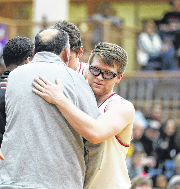 Lee Woolery|Miami Valley Today Troy seniors Sam Shaneyfelt and Chris DeMeo embrace Troy boys basketball coach Paul Bremigan after Thursday's loss in the Division I sectional tournament to Springfield at Butler High School.