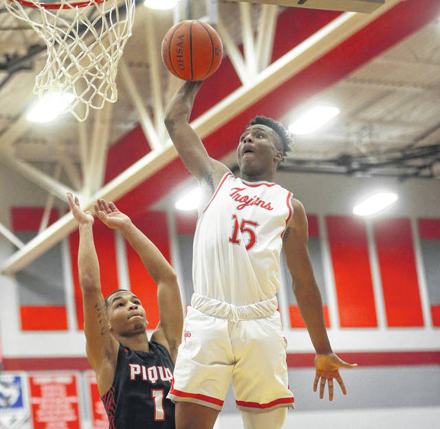 Lee Woolery Miami Valley Today file Troy's Caillou Monroe dunks the ball as Piqua's Qurri Tucker defends during a game earlier this season. The boys sectional tournament draw is at 2 p.m. Sunday.