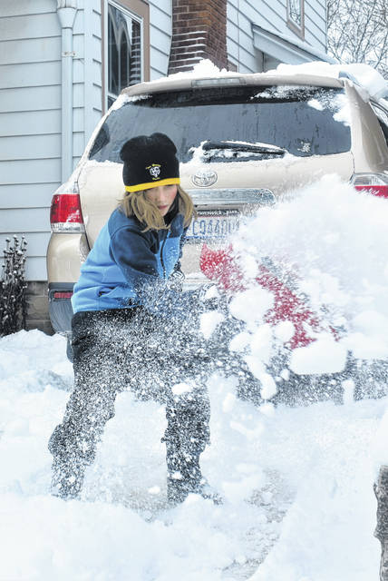Cody Willoughby | Troy Daily News Andrew Condy, 11, of Troy digs out the family vehicle following nearly 6 inches of snowfall on Friday.