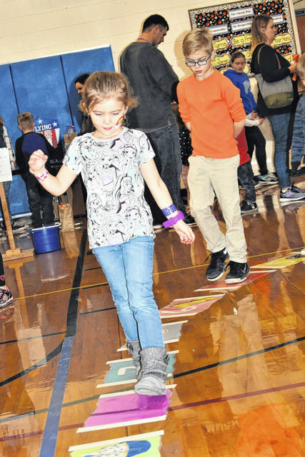 "Cody Willoughby | AIM Media Midwest Claire and Gus Richard, 5 and 9, stroll along the cake walk during ""Vikingfest"" on Saturday at Miami East Local Schools."