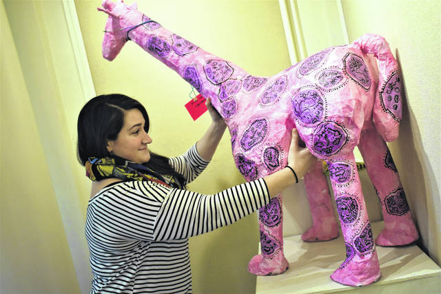"Cody Willoughby | AIM Media Midwest Troy Junior High art instructor Gabbie Braun scoots a giraffe sculpture into place in preparation for the ""Young Masters"" exhibit, which opens Friday, Feb. 22 at Troy-Hayner Cultural Center."
