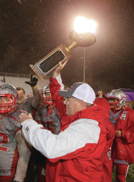 Lee Woolery | Miami Valley Today file photo Troy High School athletic director Dave Palmer awards the Traditions Trophy to the Troy football team after its victory over rival Piqua in 2017. Palmer now will lead the search for a new head football coach after Matt Burgbacher announced he was leaving Troy to coach at Tippecanoe, his alma mater.