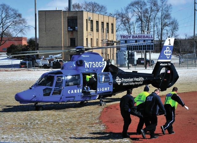 Mike Ullery | Miami Valley Today Troy Fire Department medics and CareFlight nurses transfer a Troy woman to be transported to Miami Valley Hospital following an incident on Walnut and Race streets in Troy on Monday afternoon. The woman suffered a head injury.