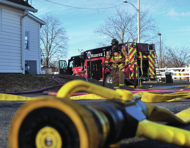 Mike Ullery | Miami Valley Today Troy firefighters work at the scene of a house fire on Sherman Avenue in Troy on Wednesday afternoon.