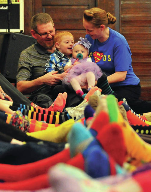 Mike Ullery | Miami Valley Today Members of the Piqua Pentecostal Church display their brightly-colored socks worn in support of church member Abel Saunders, 4, for World Down syndrome Awareness Day at the church. Church members Chris and Amanda Saunders, top center with Abel, began recognizing World Down syndrome Awareness Day, which is on March 21, in 2017 to show support for their son, Abel.
