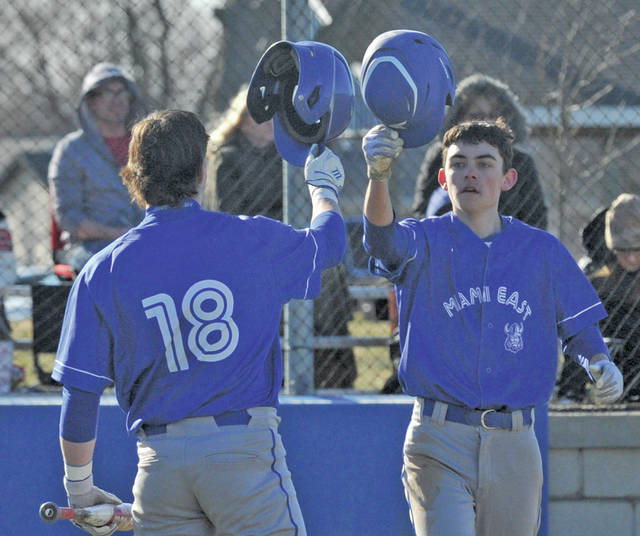 Josh Brown|Miami Valley Today Miami East's Tyler Kirby is congratulate by teammate Jonah Wolf after scoring a run Tuesday against Bradford at Miami East High School.