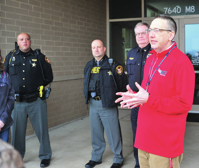 Mike Ullery | Miami Valley Today Milton-Union School superintendent Dr. Brad Ritchey, far right, addresses parents gathered at the entrance to Milton-Union High School as Friday's lockdown was lifted. With Ritchey are Deputy Warren Edmonson, SRO for Milton-Union, Capt. Jamie McGlinch, SRO supervisor for Miami County, and Harry Busse, West Milton chief of police.