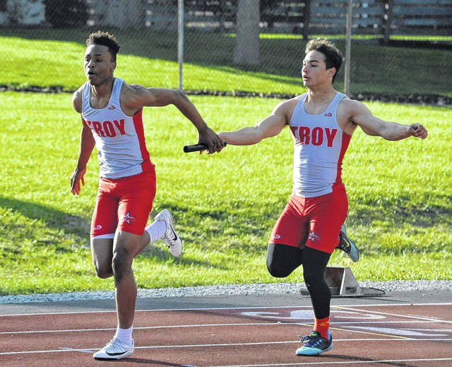 Josh Brown|Miami Valley Today file Troy's Kobe Feltner passes the baton to Caillou Monroe during a relay race last season.