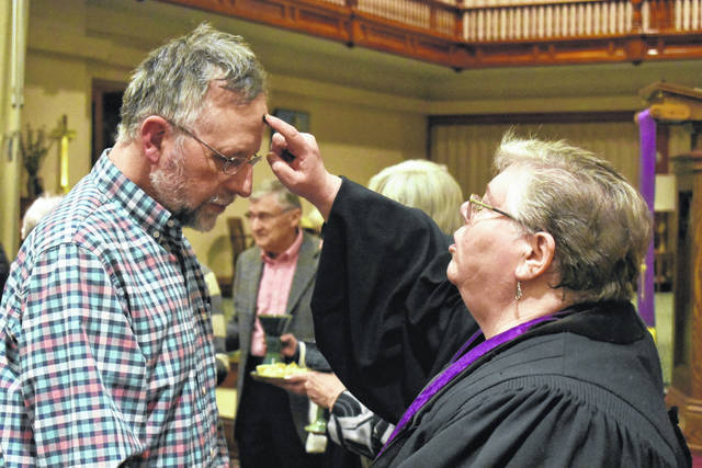 Cody Willoughby | AIM Media Midwest Roger Deeter, of Troy, receives a cross from Reverend Lauren Allen during the imposition of ashes at Troy's First United Church of Christ's special Ash Wednesday service. The congregation joined many others throughout Miami County in the sharing in Holy Communion and other Lenten practices.