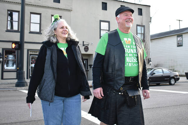 Cody Willoughby | AIM Media Midwest Gretchen Harsch and Tom Mogle, of Vandalia, march toward the registration station in their finest Irish garb during the St. Patty's Beer Crawl on Friday in Tipp City.
