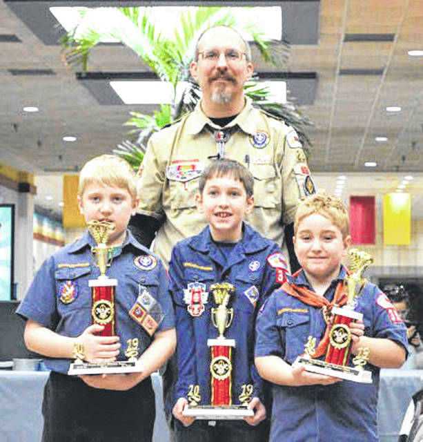 Provided photo The top three overall winners of the March 2 Pinewood Derby in Piqua, shown with with Cubmaster Adam Bishop, were Evan Brinkman (Pack 395), Anthony Frock (Pack 355) and Wade Davis (Pack 395).