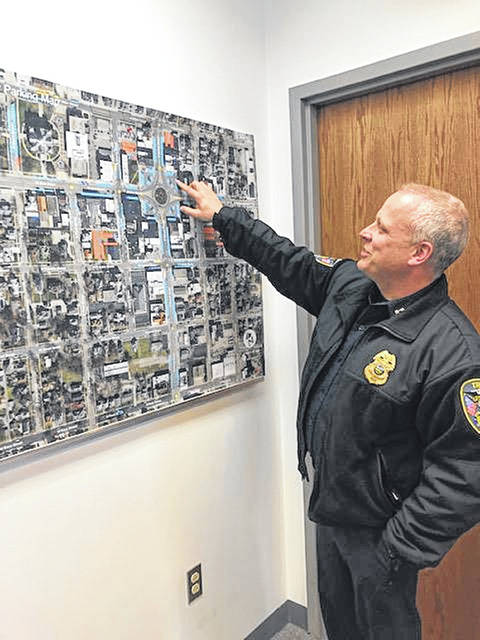 Capt. Shawn McKinney reviews the downtown parking map at the Troy Police Department last week.