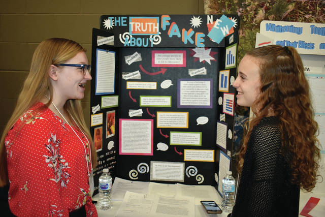 Cody Willoughby | AIM Media Midwest Sophomores Raegan Hepp and Paige Deere, of Urbana High School, discuss their project ahead of judging during the Upper Miami Valley District No. 1 Science Day on Saturday at Edison State Community College.