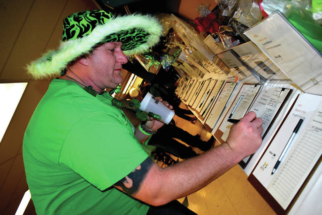 Cody Willoughby | AIM Media Midwest Kevin Swallow of Troy, adorned in his finest St. Patty's garb, participates in the silent auction during the Shamrock Shindig St. Patrick's Day Dance at St. Patrick Parish Center on Saturday in Troy.