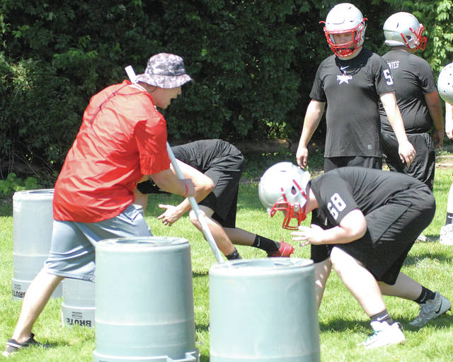 David Fong | Miami Valley Today Former Troy defensive line coach Dan Gress (left), shown here working on line drills last summer, was named the Trojans' head coach Thursday.