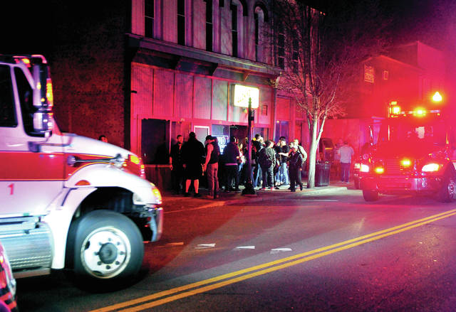 Piqua Police and Miami County Sheriff's Office deputies work to disperse a crowd as a pair of Piqua Fire Department medics arrive at Lucky's Bar on South Main Street to treat victims of a Friday night shooting that left three victims wounded.