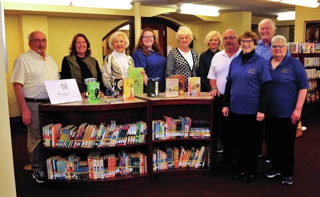 Mike Ullery | Miami Valley Today The Friends of the Piqua Public Library presented the Children's Department with two new book cases to house selections from Newbery Caldecott award-winning books. Friends of the Piqua Public Library Monty Mohler, Christine Casto, Joyce Jenkins, Susan Haas, Ruth Koon, Doug Stillwell, and Don Smith, are pictured with library staff members Nancy Spillane, Sharon Kiser, and Sarah Johnson. Not pictured: Joyce Wagner.