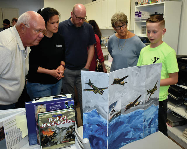 Mike Ullery | Miami Valley Today Jack Shafer, 11, far right, talks to parents and visitors about the Japanese attack on Pearly Harbor during Thursday's history open house at Miami Montessori School in Troy. Students have spent the past six weeks researching their subject and working on their presentation.
