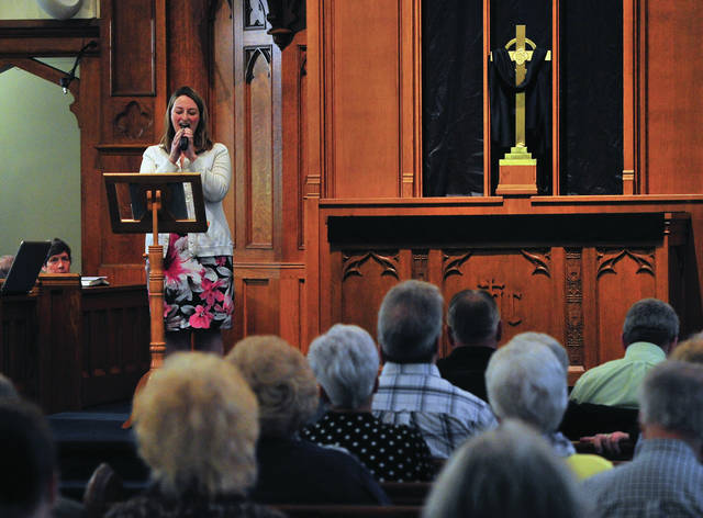 Jen Siders, top left, sings Jesus Paid it All during Friday's Community Good Friday Service at St. Paul's Evangelical & Reformed Church in Piqua