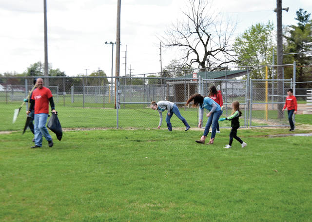 Volunteers from the Ohio Attack softball team and Kohl's clean up around the ball fields at Pitsenbarger Park in Piqua on Sunday. Kohl's Associates In Action volunteer group partnered with area the non-profit group to work on programs the help within the community.