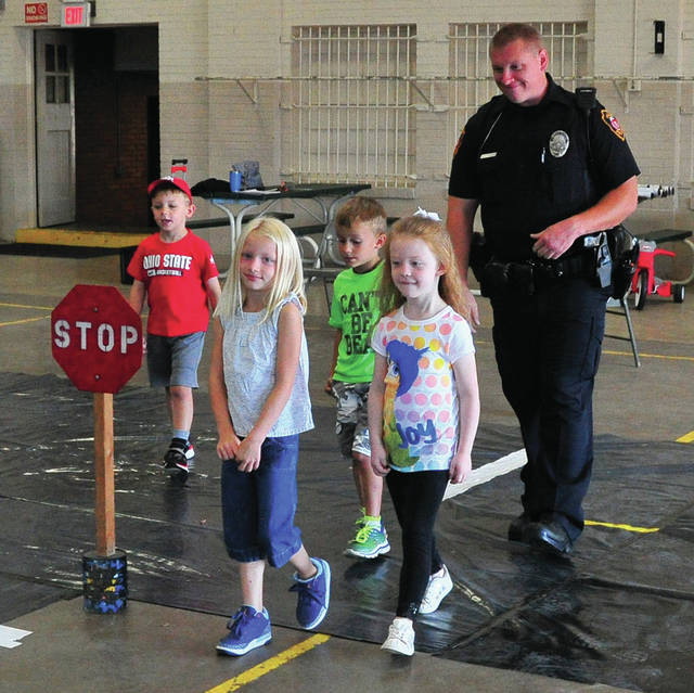 Officer Sean Stein of the Piqua Police Department watches as a group of incoming Piqua kindergarten students use a crosswalk and watch out for traffic in Safety Town 2018 at the Piqua National Guard Armory.