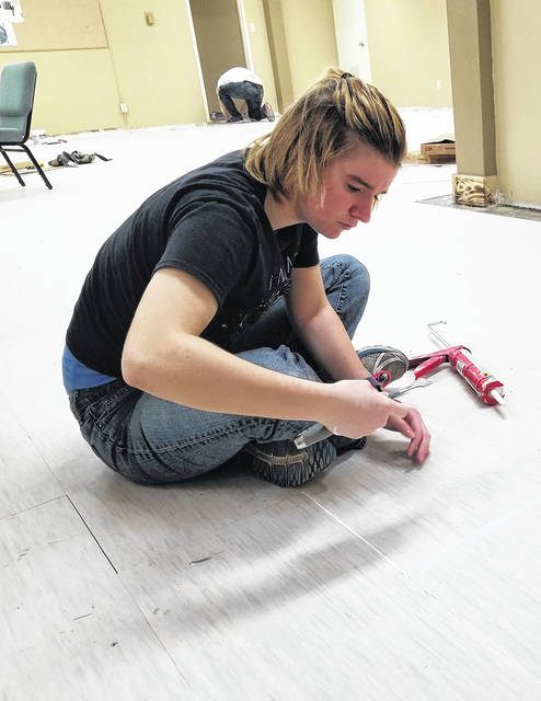 Christian Academy senior Alexandria Baughman, of Piqua, glues down flooring in the Church at Affton during a school mission trip to St. Louis, recently.