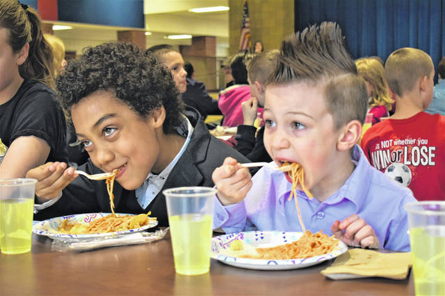 "Cody Willoughby | Miami Valley Today Sixth grader Henry Crowe and pre-schooler Aiden Walls chow down on international cuisine during the ""Celebration of Nations"" on Thursday at PCIS."