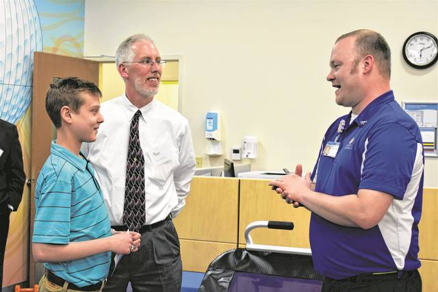 Cody Willoughby | AIM Media Midwest Patient ambassador Luke Bemus, alongside David Bemus, discuss the new Dayton Children's facility with physical therapist Mike Brennaman during the open house event on April 11.