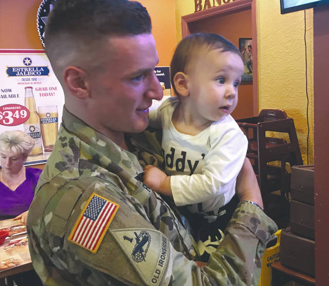 Melody Vallieu | Miami Valley Today US Army SPC Gage Fosler holds his 10-month-old daughter Emma after not having seen her in person since she was 8 days old.