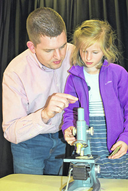 Cody Willoughby | AIM Media Midwest Matt and Alaina Giblin, of Troy, examine findings under a microscope during Family Science Night on Thursday at Heywood Elementary.