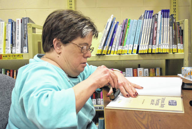 Cody Willoughby | Miami Valley Today Kathy Ludwig, of Troy, processes books for an upcoming book sale during her last shift on Tuesday at Troy-Miami County Public Library.