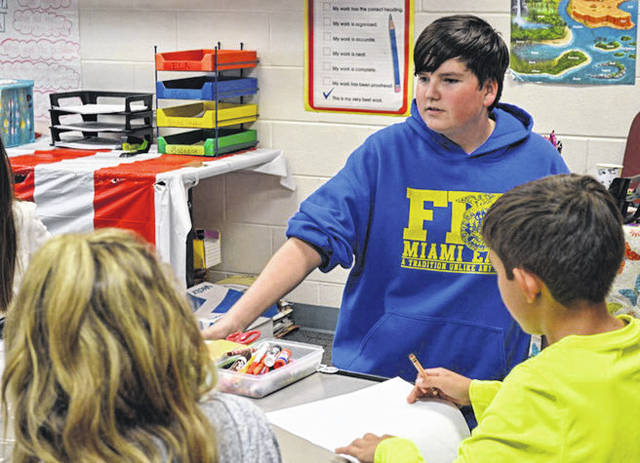 Provided photo FFA member Meadow Powers, left, works with Anna Broerman with a student in Justin Roeth's kindergarten grade class in a game of Animal Charades. Students were asked to act out an animal and their classmates could name the animal then say if it was a domestic or wild animal.