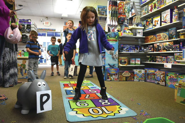 Cody Willoughby | Miami Valley Sunday News Keira Hutchings, 6, of Englewood plays Easter hopscotch on Friday during the Downtown Easter Egg Hunt in Tipp City.