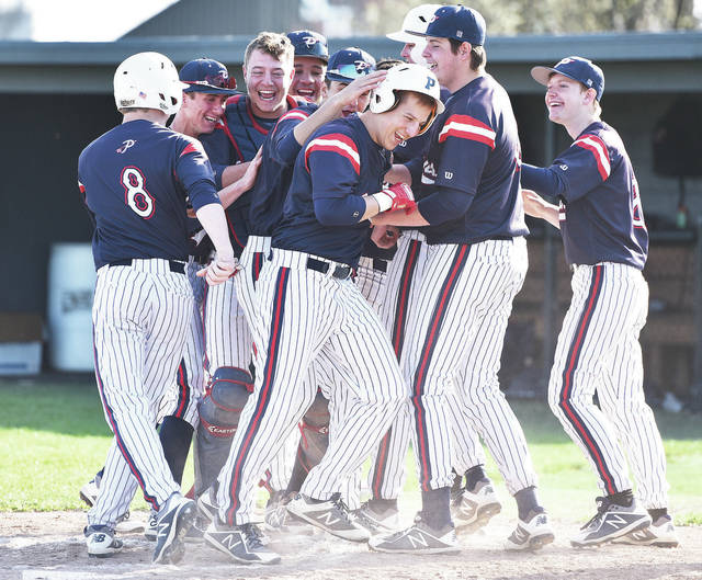Luke Gronneberg|AIM Media Piqua's Mick Karn is mobbed at home plate after hitting a grand slam Tuesday against Sidney.