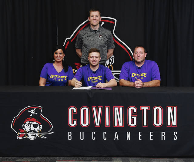 Ben Robinson|GoBuccs.com Keringten Martin signs his letter of intent to wrestle for Defiance College. Looking on are his parents Jarrod and Stacy Martin and Covington wrestling coach Eric Vanderhorst.