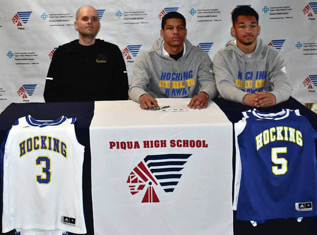 Mike Ullery|Miami Valley Today Piqua High School seniors Qurri Tucker and Trey Richmond signed their letters of intent to play basketball for Hocking College. From the left are Hocking College coach Ryan Miley, Richmond and Tucker.
